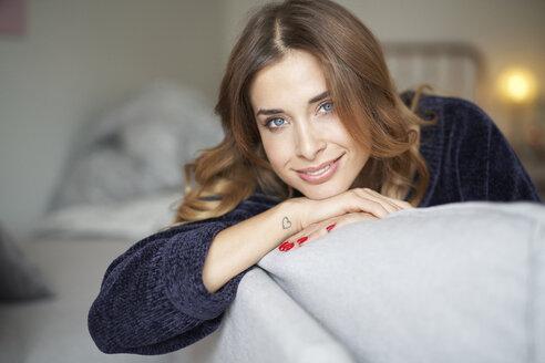 natürliches closeup beauty portrait junge frau auf sofa mit herz tattoo an handgelenk, münchen, bayern, deutschland - PNEF01310
