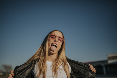 Portrait of young woman outdoors sticking out tongue - DMGF00003