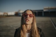 Portrait of young woman with defiant attitude wearing sunglasses outdoors - DMGF00006
