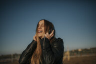Happy young woman listening music with headphones outdoors - DMGF00012