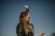 Happy young woman listening music with headphones outdoors - DMGF00021