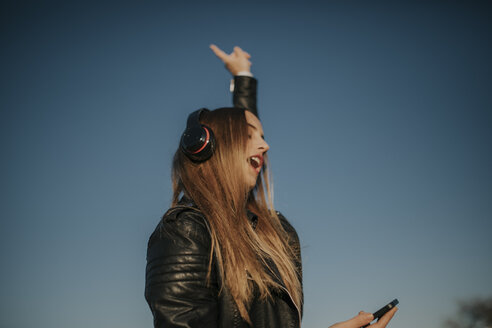 Pozoblanco, Cordoba, Spain, Urban girl listening music with headphones, youth culture - DMGF00021
