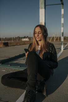 Pozoblanco, Cordoba, Spain, Sitting urban girl listening music with headphones, youth culture - DMGF00024