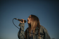 Young woman singing with a microphone under blue sky - DMGF00036