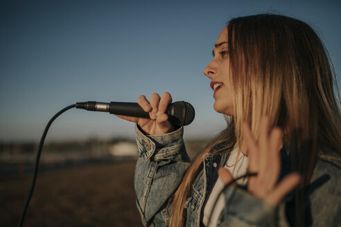 Pozoblanco, Cordoba, Spain, Urban girl singing with a microphone in the hand, youth culture - DMGF00039