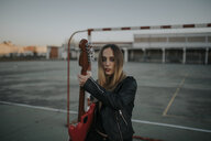 Portrait of cool young woman with guitar on sports field - DMGF00051