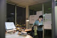 Businesswoman with digital tablet working late in office - HEROF16692