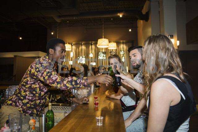Bartender and friends toasting beer bottles at bar - HEROF16728