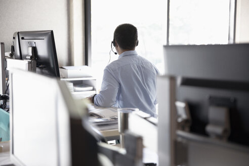 Businessman with headset working in cubicle - HEROF16824