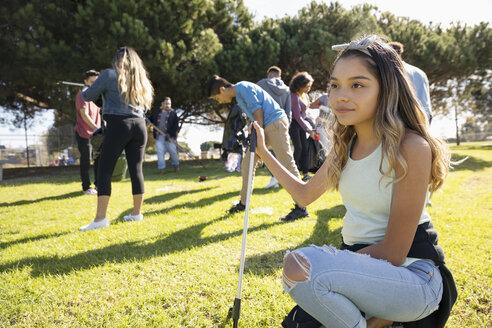 Confident Latinx girl volunteering, cleaning sunny park - HEROF16890