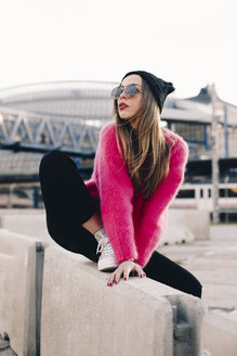 Portrait of fashionable young woman wearing sunglasses, cap and pink knit pullover - ACPF00429