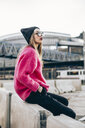 Portrait of fashionable young woman wearing sunglasses, cap and pink knit pullover - ACPF00432