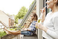 Young couple sitting on their balcony in summer, man using laptop - PESF01102