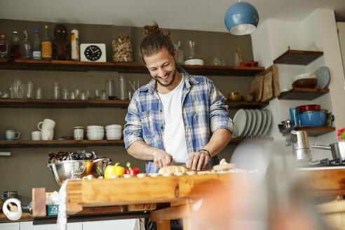 Young man preparing food at home, slicing bread - PESF01108