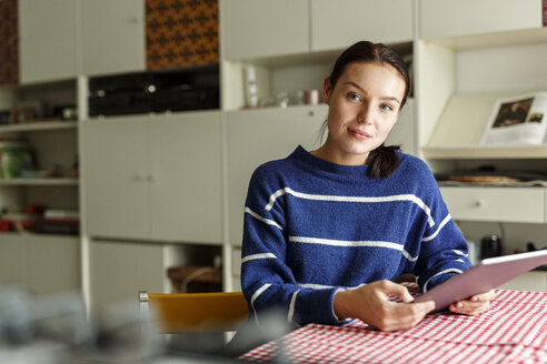 Young woman sitting at home, using digital tablet - PESF01132