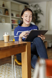 Young woman sitting at home, using digital tablet - PESF01138