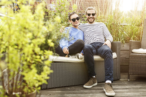 Young couple relaxing on their balcony, sitting on couch - PESF01156