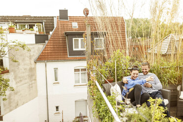 Young couple relaxing on their balcony, sitting on couch - PESF01159