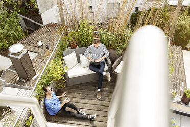 Young couple relaxing on their balcony, sitting on couch, using laptop - PESF01165