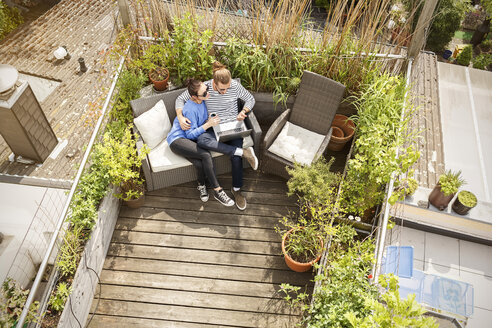 Young couple relaxing on their balcony, sitting on couch, using laptop - PESF01168