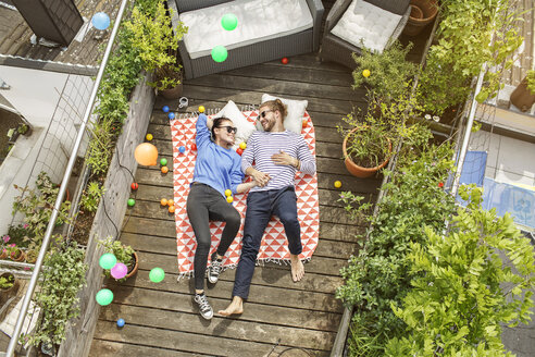 Young couple relaxing on their balcony, lying on blanket with arms around - PESF01171