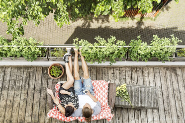 Young couple relaxing on their balcony in summer, drinking coffee - PESF01180