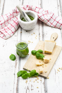 Glass of homemade pesto Genovese, ingredients, mortar and kitchen towel - LVF07752