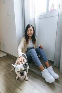 Young woman sitting on ground, stroking pug - KIJF02265
