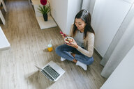 Young woman sitting on floor, using smartphone - KIJF02268