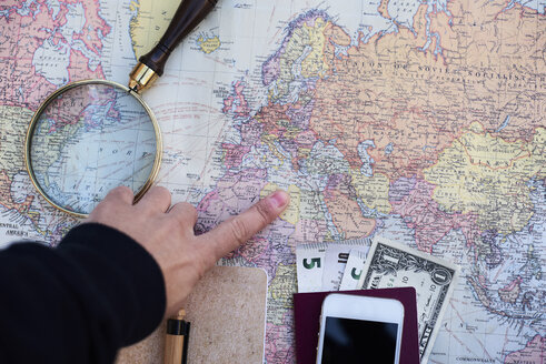 Travel planning with a world map, money, cell phone and magnifying glass - IGG00749