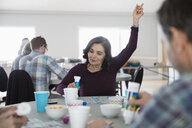 Senior woman playing bingo, winning with arm raised in community center - HEROF17004