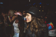 Smiling, confident young female millennial enjoying music concert in nightclub - HEROF17022