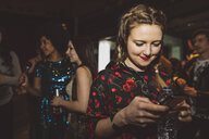 Smiling female millennial texting with smart phone in nightclub - HEROF17028