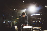 Rockabilly musician preparing, tightening drums on stage - HEROF17034