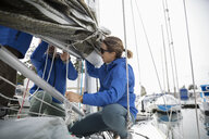 Sailing team preparing sail on sailboat in harbor - HEROF17085