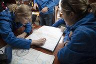 Sailing team plotting course at map on sailboat - HEROF17088