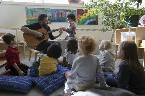 Preschool students listening to male teacher playing guitar in classroom - HEROF17172