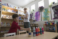 Preschool teacher and boy student preparing paint for art project - HEROF17181