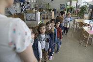 Preschool students lining up for teacher in classroom - HEROF17223