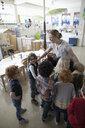 Preschool students hugging happy teacher in classroom - HEROF17229