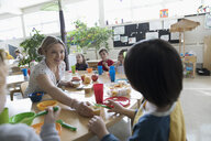 Preschool teacher and students eating during snack time in classroom - HEROF17247