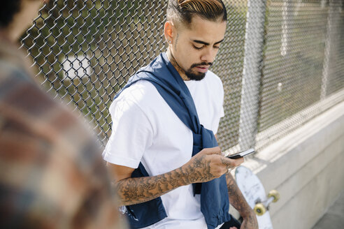 Latinx young man with tattoos texting with smart phone - HEROF17376