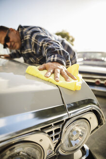 Latinx man waxing vintage car - HEROF17412