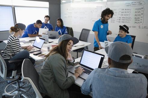 Hackers using laptops, talking during hackathon - HEROF17463
