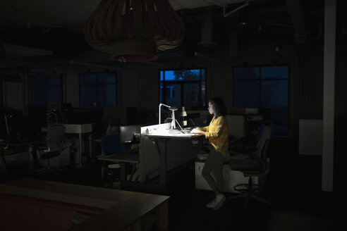 Businesswoman working late at sit-stand desk in dark office - HEROF17484