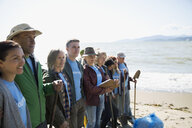 Beach cleanup volunteers standing in a row on beach - HEROF17496