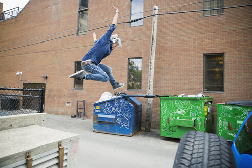 Cool young man jumping off ledge in urban alley - HEROF17535