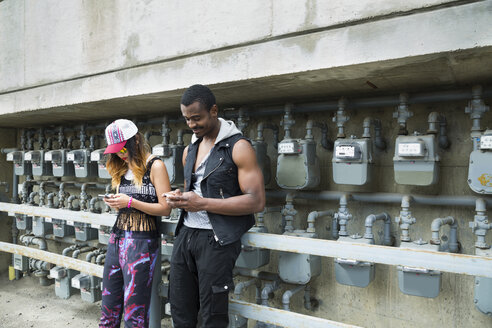 Cool young couple texting with cell phones at electric meters - HEROF17544