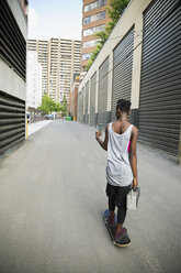 Cool young woman skateboarding with boom box and texting in urban alley - HEROF17547