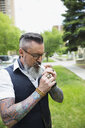 Cool hipster with gray beard and tattoos smoking cigarette in urban park - HEROF17568